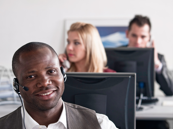 Young man sitting behind a desk in the customer support center and talking on the phone, in the blurred background other office workers are sitting and working.