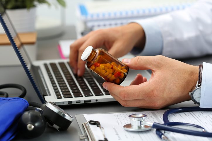 Male medicine doctor hands hold jar of pills and type something on laptop computer keyboard. Panacea and life save, prescribing treatment, legal drug store, take stock, consumption statistics concept
