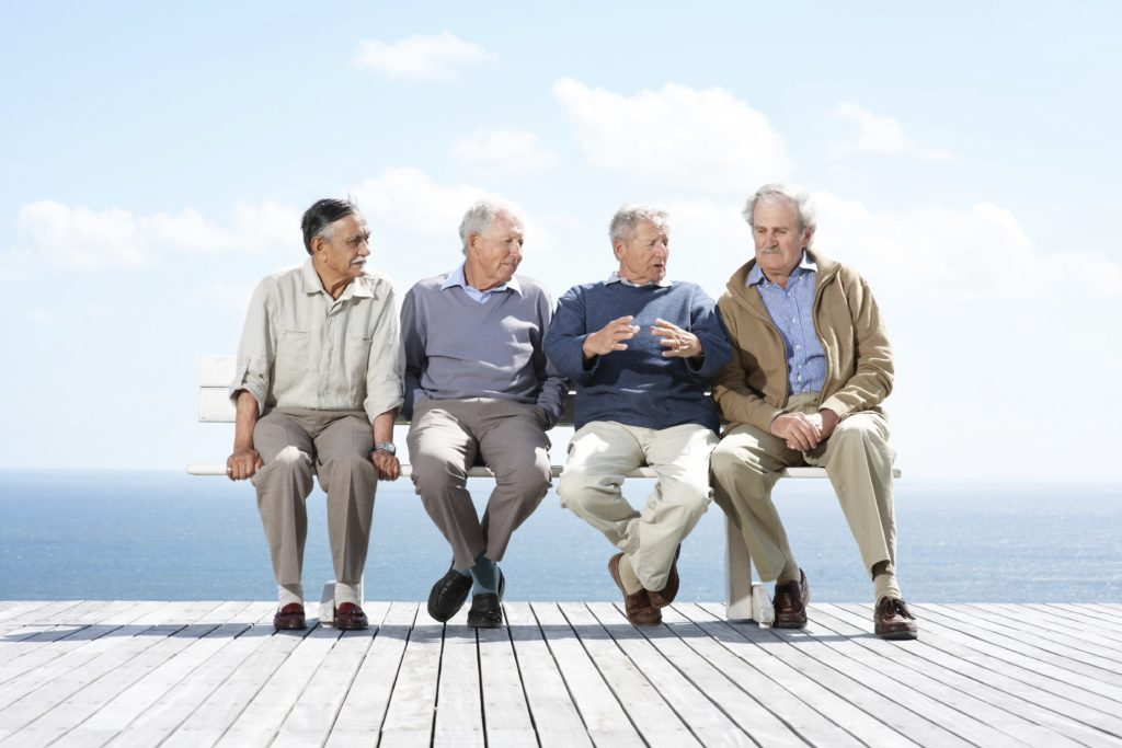 Four elderly men talking while sitting on a bench on a deck by the ocean