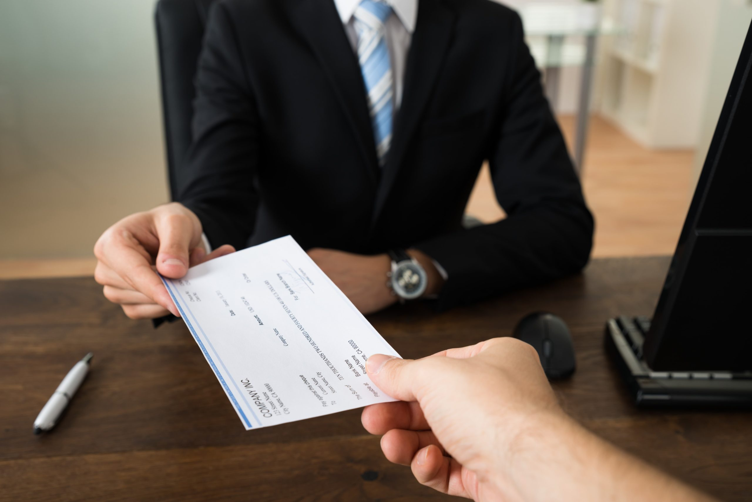 Person handing a check to a man