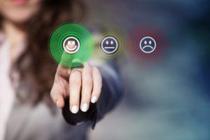 Person selecting a green smiley face